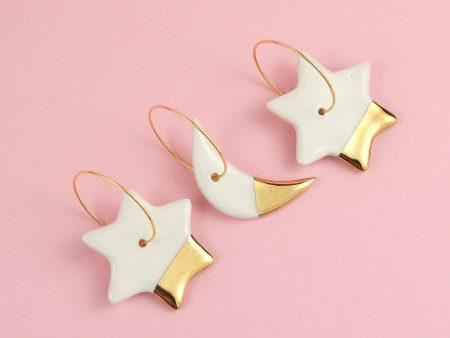 Cercei câte 3 asimetrici, lună și stele, din ceramică decorată cu aur. Steluță 2,5 cm. Lungime lună 3 cm. Închizătoare inox auriu 2,5 cm. Gruni