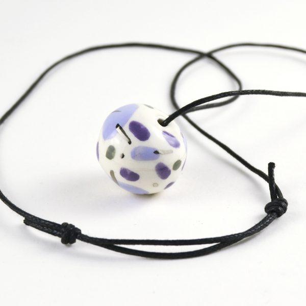 Colier cu mărgea ceramică mov / platină, modelată și pictată manual, pe fir cu noduri culisante. Mărgea 2,8 x 2 cm. Deschidere max 38 cm.