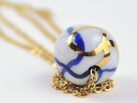 Colier fulger globular cu mărgea din porţelan, modelată și decorată cu aur. Lănțișor de inox auriu 45 cm. Gruni