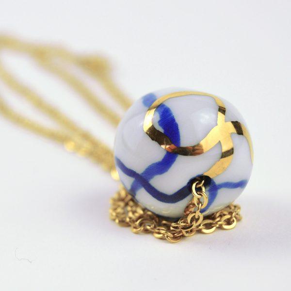 Pandantiv din porţelan cu fulger globular, modelată și decorată cu aur. Mărgea 2 cm. Lănțișor de inox auriu 60 cm. Gruni