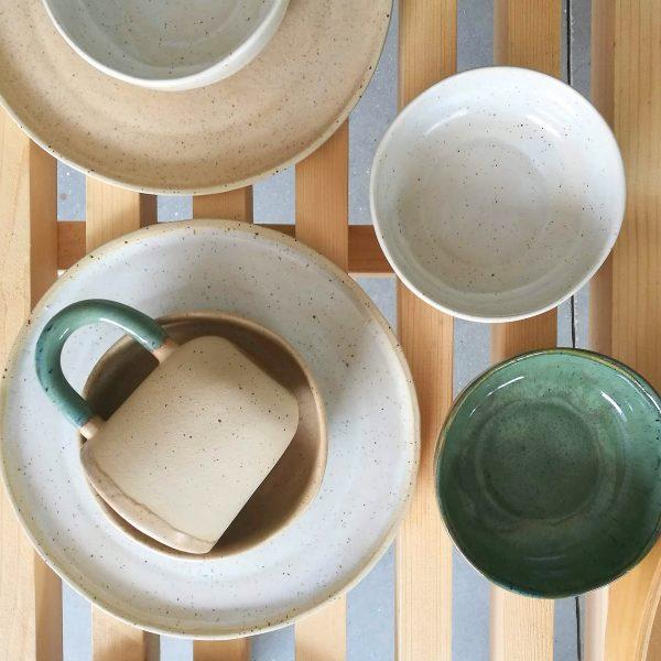 Cană de cafea, cu toartă, handmade din gresie ceramică, seria Mix&Match Natur. Manufacturată din ceramică de temperatură înaltă, cu picăţele, parţial glazurată. Partea neglazurată are porii complet închişi ceea ce o face rezistentă la murdărie şi la pătare. Mâner verde, interior caramel. Diametru de 10 de cm şi adâncime de 13.