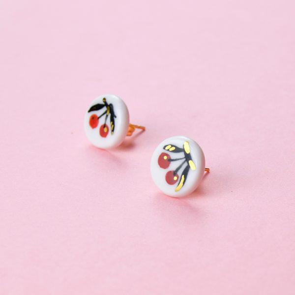 Cercei mici cu cireșe pictate manual pe ceramică, decorație cu aur. Tijă inox sau argint placat cu aur. Diametru 1 cm. Design proaspăt, nepretențios, cu fructe. Gruni