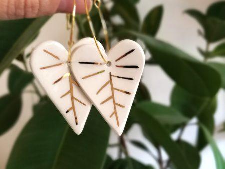 Cercei frunze albe, de iarnă, din ceramică, modelați și decorați cu aur. Închizătoare inox auriu. 3,2 x 7,5 cm. 8 g / perechea. Design Gruni