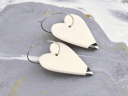 Cercei inimă ceramică, cu vârf pictat manual cu aur/platină față-verso. Închizătoare inox. 2,5 x 7 cm. 10 g / perechea. Bijuterie de autor.