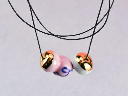 Colier fulger globular cu mărgea roz din porțelan pictată manual cu aur. Dimensiuni 2x2x6 cm. Fir negru de bumbac cerat cu nod culisant. Design Gruni.