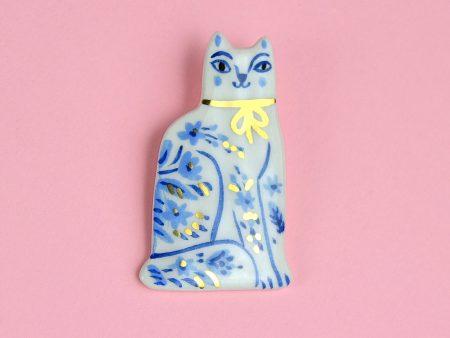 Broșă cu pin, Pisică din Delft, din ceramică pictată manual cu flori albastre și decorată cu aur. 3 x 5 cm, 7 g. Închizătoare alamă. Gruni.