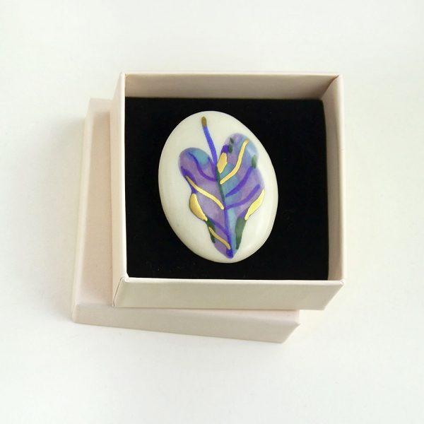 Broșă unicat cu frunză albastră de alocasia, ceramică pictată manual, decorată cu aur. Dimensiune 3,5 x 4,5 cm. Pin alamă. Gruni.