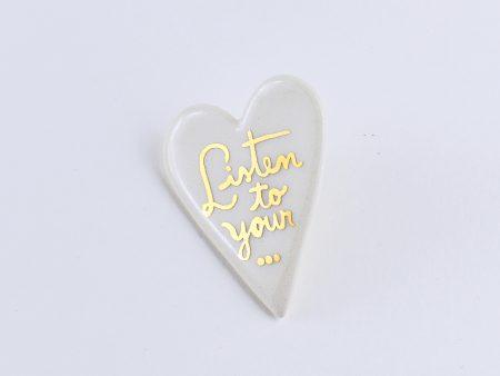Broşă inimă, cu textul Listen to your... scris manual cu aur pe ceramică albă. Pin alamă pentru haine groase. 3 x 4 cm, 7 g. Design Gruni. Unicat