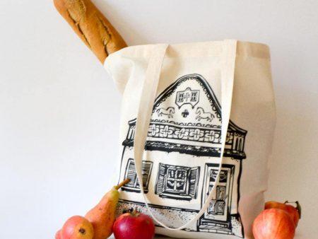 Sacoșă bumbac nealbit cu desen casă șvăbească tradițională din Banat. Imprimat serigrafic. Dimensiuni 37 x 41 cm, mânere 39 cm.
