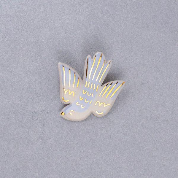 Broșă tip pin pasăre în zbor, ceramică pictată manual, decorată cu aur. Dimensiune 6,5 x 6,5 cm. Pin alamă. Pentru haine groase.