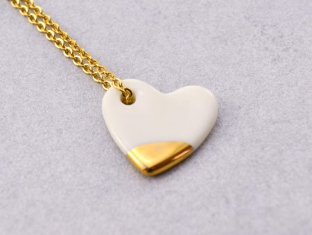 Colier cu inimioară din porțelan cu un accent pictat manual cu aur. Dimensiuni 1,2 x 1,2 cm. Greutate 4g. Lănțișor inox auriu, 45 cm. Gruni