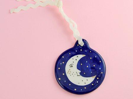 Ornament albastru cu semilună, pentru pomul de Crăciun, cu ocazia sărbătorilor de iarnă. Dimensiuni 6 x 7 cm. Pictat cu albastru pentru a descrie silueta unei semilune personificate. Pictat și decorat manual cu aur pe ceramică, pe ambele fețe.