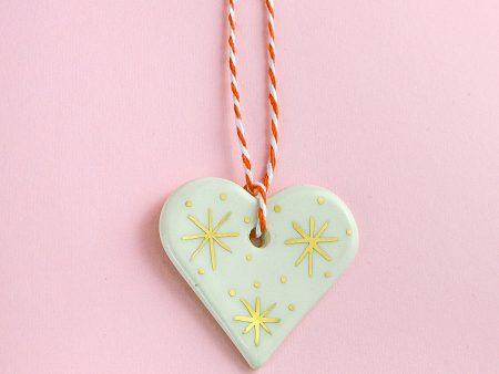 Ornament inimioară albă, pentru pomul de Crăciun. 5 x 5 cm. Decorată manual cu aur pe ceramică. Unicat. Gruni
