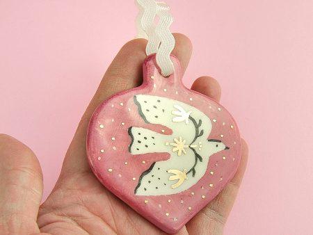 Ornament roz cu pasăre în zbor, pentru pomul de Crăciun. Dimensiuni 7 x 8 cm. Pictat și decorat manual cu aur pe ceramică, la Gruni.