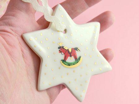 Ornament Stea cu un căluț, pentru pomul de Crăciun. 8 x 8 cm. Pictat manual cu un căluț de jucărie. Decorat cu aur pe ceramică. Unicat.