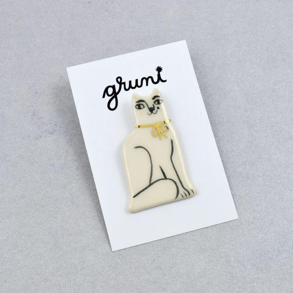 Broşă ceramică tip pin pisică albă, desenată manual cu negru. 3 x 5 cm, 7 g. Pin alamă. Potrivit pentru haine groase. Design Gruni.